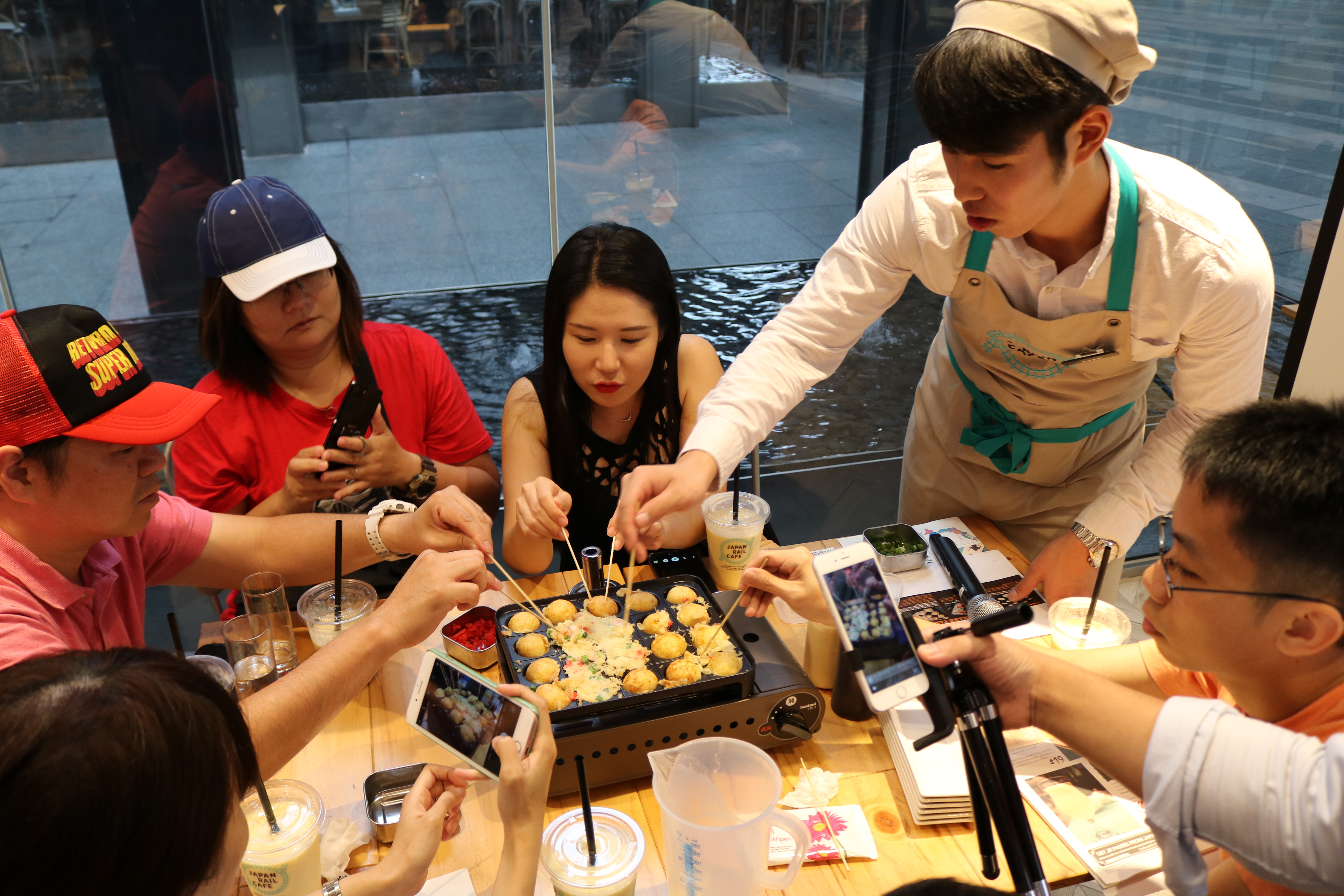 Travel Communicator Chiro demonstrating to participants how to make takoyaki!